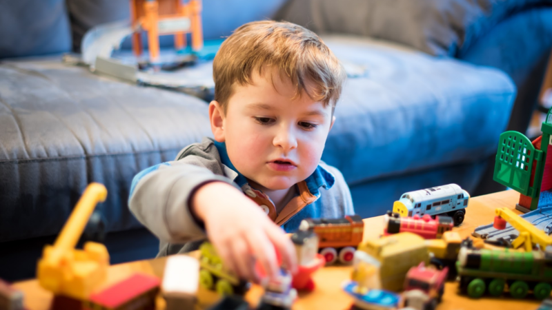 A small child playing with his toys on a coffee table.